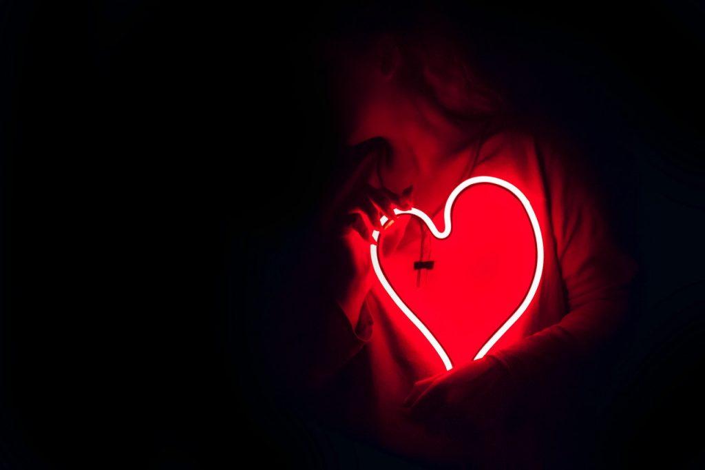 Femme dans le noir tenant un cœur lumineux néon