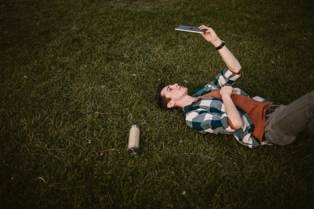 Homme allongé dans l'herbe  faisant un appel vidéo sur une tablette