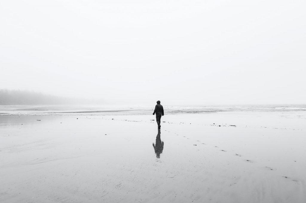 Photo en noir et blanc d'une personne marchant au bord de la plage
